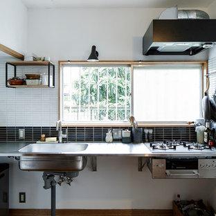 横浜のアジアンスタイルのおしゃれなL型キッチン (一体型シンク、ルーバー扉のキャビネット、ステンレスカウンター、黒いキッチンパネル、モザイクタイルのキッチンパネル、シルバーの調理設備の、茶色い床、グレーのキッチンカウンター、濃色木目調キャビネット、濃色無垢フローリング) の写真
