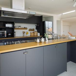 東京23区のコンテンポラリースタイルのおしゃれなキッチン (シングルシンク、フラットパネル扉のキャビネット、黒いキャビネット、木材カウンター、グレーの床) の写真