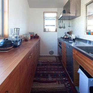 東京23区の中サイズの北欧スタイルのおしゃれなキッチン (一体型シンク、シェーカースタイル扉のキャビネット、中間色木目調キャビネット、ステンレスカウンター、白いキッチンパネル、セラミックタイルのキッチンパネル、シルバーの調理設備の、カーペット敷き、マルチカラーの床) の写真