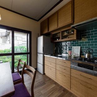 他の地域の中サイズの北欧スタイルのおしゃれなキッチン (シングルシンク、フラットパネル扉のキャビネット、中間色木目調キャビネット、ステンレスカウンター、緑のキッチンパネル、セラミックタイルのキッチンパネル、濃色無垢フローリング、茶色い床) の写真