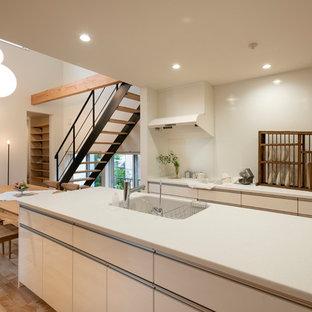 名古屋のモダンスタイルのおしゃれなキッチン (白いキャビネット、人工大理石カウンター、白いキッチンパネル、淡色無垢フローリング、ベージュの床、白いキッチンカウンター) の写真