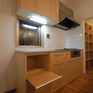他の地域のアジアンスタイルのおしゃれなキッチン (一体型シンク、ステンレスカウンター、白いキッチンパネル、磁器タイルのキッチンパネル、シルバーの調理設備の、無垢フローリング) の写真