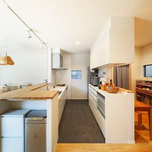 Modelo de cocina lineal, nórdica, abierta, con fregadero de un seno, armarios con paneles lisos, puertas de armario blancas, salpicadero blanco, península y suelo negro