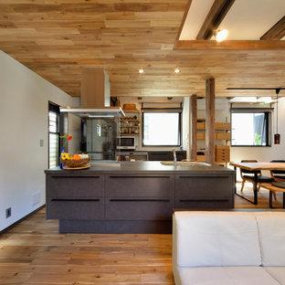 他の地域のアジアンスタイルのおしゃれなキッチン (一体型シンク、フラットパネル扉のキャビネット、茶色いキャビネット、ステンレスカウンター、シルバーの調理設備、無垢フローリング、茶色い床) の写真