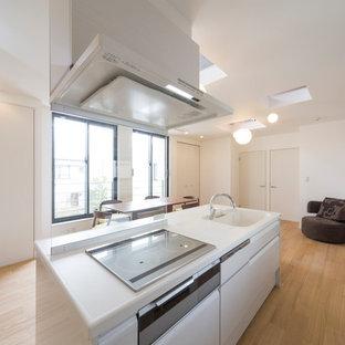 東京23区のコンテンポラリースタイルのおしゃれなアイランドキッチン (一体型シンク、フラットパネル扉のキャビネット、白いキャビネット、淡色無垢フローリング、ベージュの床、白いキッチンカウンター) の写真