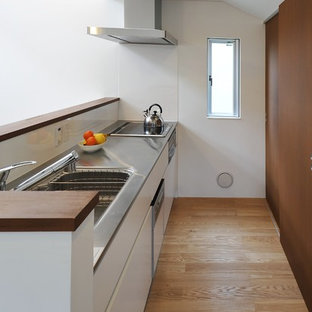 Mid-sized contemporary single-wall open plan kitchen in Tokyo with an integrated sink, flat-panel cabinets, white cabinets, stainless steel benchtops, white splashback, slate splashback, stainless steel appliances, plywood floors and brown floor.