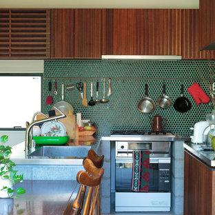 東京23区のミッドセンチュリースタイルのおしゃれなキッチン (シングルシンク、フラットパネル扉のキャビネット、中間色木目調キャビネット、ステンレスカウンター、緑のキッチンパネル、セラミックタイルのキッチンパネル) の写真