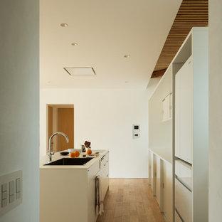 Offene, Einzeilige Asiatische Küche mit Unterbauwaschbecken, weißen Schränken, Kupfer-Arbeitsplatte, Küchenrückwand in Weiß, weißen Elektrogeräten, hellem Holzboden und Kücheninsel in Sonstige