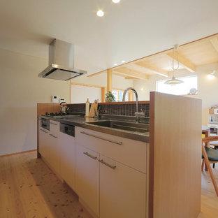 他の地域の北欧スタイルのおしゃれなキッチン (一体型シンク、フラットパネル扉のキャビネット、淡色木目調キャビネット、ステンレスカウンター、茶色いキッチンパネル、モザイクタイルのキッチンパネル、シルバーの調理設備の、淡色無垢フローリング) の写真