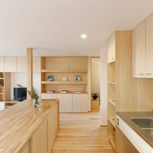 東京都下の広いアジアンスタイルのおしゃれなキッチン (一体型シンク、フラットパネル扉のキャビネット、淡色木目調キャビネット、ステンレスカウンター、シルバーの調理設備、淡色無垢フローリング、ベージュの床、グレーのキッチンカウンター) の写真