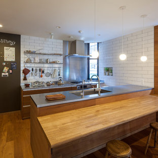 Photo of an asian galley open plan kitchen in Osaka with an undermount sink, flat-panel cabinets, medium wood cabinets, stainless steel benchtops, white splashback, stainless steel appliances, medium hardwood floors and a peninsula.