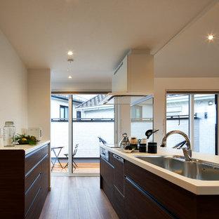 他の地域のミッドセンチュリースタイルのおしゃれなキッチン (シングルシンク、フラットパネル扉のキャビネット、濃色木目調キャビネット、無垢フローリング、茶色い床) の写真