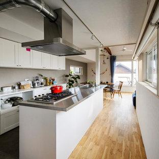 北欧スタイルのおしゃれなキッチン (シングルシンク、落し込みパネル扉のキャビネット、白いキャビネット、ステンレスカウンター、淡色無垢フローリング、茶色い床) の写真