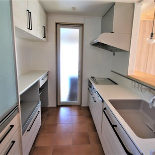 Small industrial single-wall open plan kitchen in Other with a single-bowl sink, flat-panel cabinets, grey cabinets, solid surface benchtops, white splashback, slate splashback, stainless steel appliances, linoleum floors, no island, brown floor and grey benchtop.