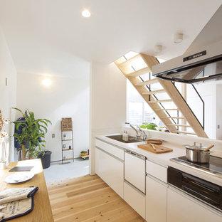 他の地域の北欧スタイルのおしゃれなキッチン (シングルシンク、フラットパネル扉のキャビネット、白いキャビネット、淡色無垢フローリング、茶色い床) の写真