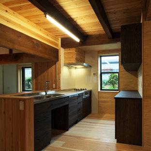 Aménagement d'une cuisine linéaire asiatique avec un évier 1 bac, un placard à porte plane, des portes de placard noires, un sol en bois brun, une péninsule et un sol marron.