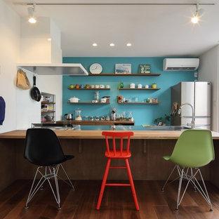 Einzeilige, Offene Eklektische Küche mit Edelstahl-Arbeitsplatte, integriertem Waschbecken, braunem Holzboden, Halbinsel und braunem Boden in Sonstige