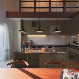 他の地域の広いコンテンポラリースタイルのおしゃれなキッチン (アンダーカウンターシンク、インセット扉のキャビネット、グレーのキャビネット、ステンレスカウンター、緑のキッチンパネル、ガラス板のキッチンパネル、パネルと同色の調理設備、クッションフロア、ベージュの床、オレンジのキッチンカウンター) の写真