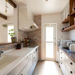 他の地域の小さい地中海スタイルのおしゃれなキッチン (一体型シンク、フラットパネル扉のキャビネット、グレーのキャビネット、人工大理石カウンター、茶色いキッチンパネル、セメントタイルのキッチンパネル、シルバーの調理設備、白いキッチンカウンター、茶色い床) の写真