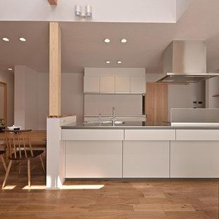 他の地域の和風のおしゃれなキッチン (一体型シンク、フラットパネル扉のキャビネット、白いキャビネット、ステンレスカウンター、無垢フローリング、茶色い床、白いキッチンパネル、白いキッチンカウンター) の写真