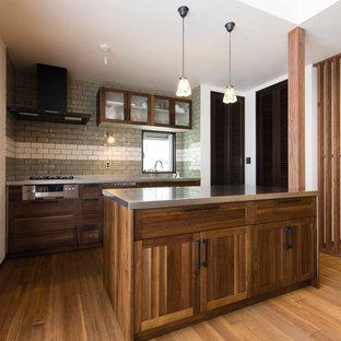 他の地域のカントリー風おしゃれなアイランドキッチン (落し込みパネル扉のキャビネット、ヴィンテージ仕上げキャビネット、ステンレスカウンター、無垢フローリング、茶色い床) の写真