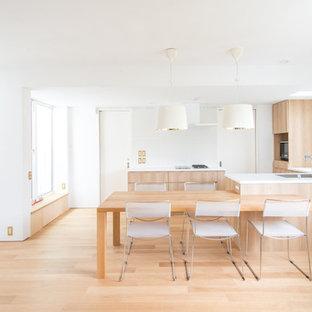 東京23区の北欧スタイルのおしゃれなキッチン (アンダーカウンターシンク、インセット扉のキャビネット、中間色木目調キャビネット、人工大理石カウンター、白いキッチンパネル、磁器タイルのキッチンパネル、黒い調理設備、淡色無垢フローリング、ベージュの床、ベージュのキッチンカウンター) の写真