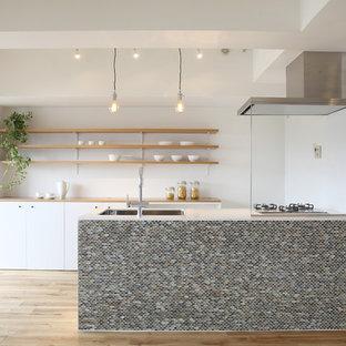 Cette image montre une cuisine parallèle nordique avec un évier 1 bac, un placard à porte plane, des portes de placard blanches, un sol en bois clair et un îlot central.