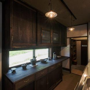 Geschlossene, Einzeilige Asiatische Küche mit Unterbauwaschbecken, flächenbündigen Schrankfronten, braunen Schränken, Edelstahl-Arbeitsplatte, Küchenrückwand in Weiß, bunten Elektrogeräten, Betonboden, zwei Kücheninseln und grauem Boden in Sonstige