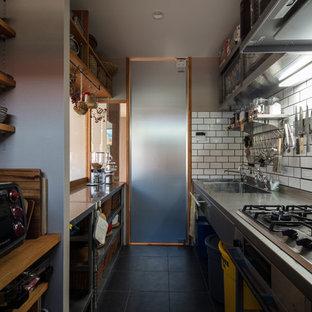 他の地域のアジアンスタイルのおしゃれなキッチン (ダブルシンク、オープンシェルフ、ステンレスカウンター、白いキッチンパネル、磁器タイルのキッチンパネル、シルバーの調理設備の、磁器タイルの床、黒い床) の写真