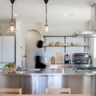 他の地域, の北欧スタイルのおしゃれなキッチン (一体型シンク、フラットパネル扉のキャビネット、ステンレスキャビネット、ステンレスカウンター、無垢フローリング、茶色い床) の写真