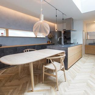 北欧スタイルのおしゃれなキッチン (アンダーカウンターシンク、インセット扉のキャビネット、淡色木目調キャビネット、グレーのキッチンパネル、シルバーの調理設備、ベージュの床、淡色無垢フローリング) の写真