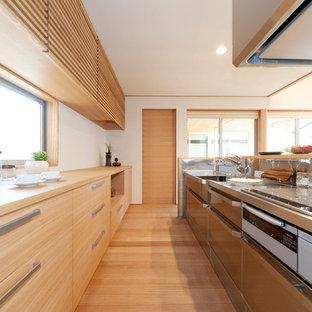 他の地域のモダンスタイルのおしゃれなキッチン (ステンレスカウンター、淡色無垢フローリング、ベージュの床、ベージュのキッチンカウンター) の写真