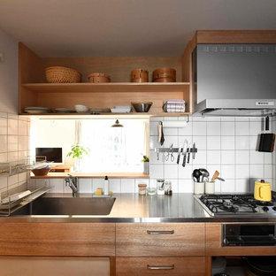 他の地域の北欧スタイルのおしゃれなキッチン (一体型シンク、フラットパネル扉のキャビネット、中間色木目調キャビネット、ステンレスカウンター、白いキッチンパネル、セラミックタイルのキッチンパネル) の写真
