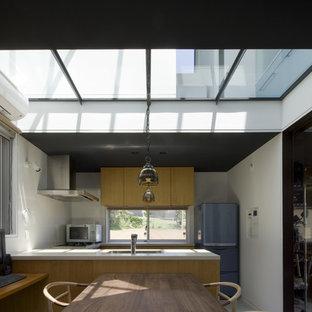 他の地域の中くらいのモダンスタイルのおしゃれなキッチン (アンダーカウンターシンク、フラットパネル扉のキャビネット、中間色木目調キャビネット、人工大理石カウンター、白いキッチンパネル、セラミックタイルのキッチンパネル、シルバーの調理設備、セラミックタイルの床、グレーの床、ベージュのキッチンカウンター) の写真