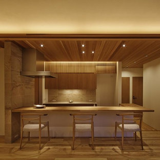Asian galley open plan kitchen in Kyoto with flat-panel cabinets, medium wood cabinets, wood benchtops, beige splashback, medium hardwood floors, a peninsula and brown floor.