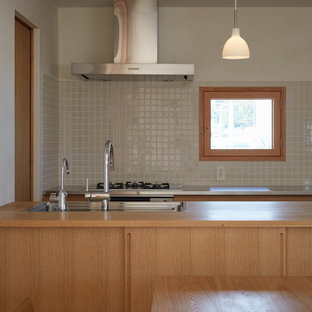 Inspiration for a mid-sized asian galley open plan kitchen in Other with an undermount sink, flat-panel cabinets, light wood cabinets, wood benchtops, white splashback, porcelain splashback, stainless steel appliances, medium hardwood floors, multiple islands, brown floor and beige benchtop.