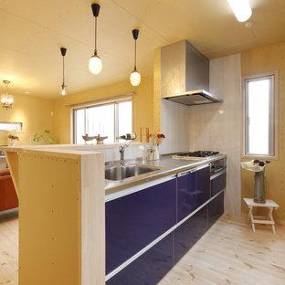 他の地域のエクレクティックスタイルのおしゃれなキッチン (シングルシンク、青いキャビネット、ステンレスカウンター、淡色無垢フローリング、フラットパネル扉のキャビネット、白いキッチンパネル、茶色い床) の写真