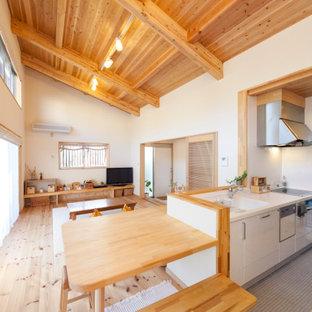 他の地域のアジアンスタイルのおしゃれなキッチン (フラットパネル扉のキャビネット、白いキャビネット、シルバーの調理設備、淡色無垢フローリング、ベージュの床、白いキッチンカウンター) の写真