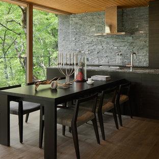 他の地域のラスティックスタイルのおしゃれなキッチン (ダブルシンク、フラットパネル扉のキャビネット、黒いキャビネット、グレーのキッチンパネル、無垢フローリング、茶色い床、グレーのキッチンカウンター) の写真