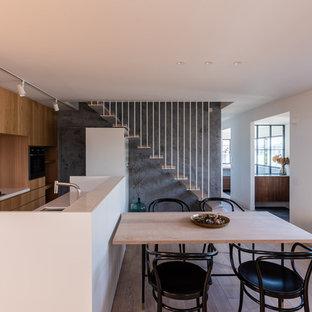 他の地域のコンテンポラリースタイルのおしゃれなキッチン (アンダーカウンターシンク、フラットパネル扉のキャビネット、中間色木目調キャビネット、白いキッチンパネル、茶色い床、白いキッチンカウンター、淡色無垢フローリング) の写真