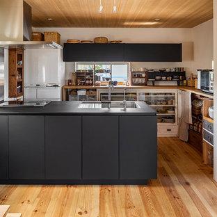 東京23区の北欧スタイルのおしゃれなキッチン (アンダーカウンターシンク、インセット扉のキャビネット、グレーのキャビネット、メタリックのキッチンパネル、シルバーの調理設備、無垢フローリング、茶色い床、黒いキッチンカウンター) の写真