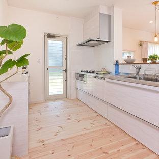 他の地域の北欧スタイルのおしゃれなキッチン (シングルシンク、ベージュのキャビネット、白いキッチンパネル、黒い調理設備、淡色無垢フローリング、フラットパネル扉のキャビネット、ステンレスカウンター、ベージュの床) の写真