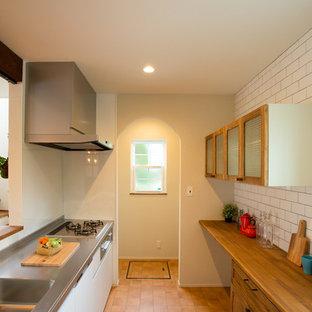 Exemple d'une cuisine linéaire asiatique avec un évier 1 bac, un placard à porte plane, des portes de placard blanches, un plan de travail en inox, une crédence blanche, un sol en carreau de terre cuite, une péninsule, un sol orange et un plan de travail marron.