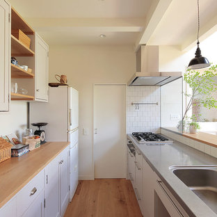 Inspiration for a scandinavian single-wall open plan kitchen in Yokohama with an integrated sink, recessed-panel cabinets, white cabinets, wood benchtops, white splashback, white appliances, medium hardwood floors, a peninsula and brown floor.