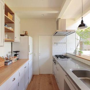 横浜のI型北欧風 LDKの画像 (一体型シンク、落し込みパネル扉のキャビネット、白いキャビネット、木材カウンター、白いキッチンパネル、白い調理設備、無垢フローリング、ペニンシュラキッチン、茶色い床)