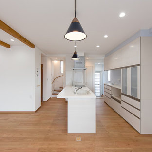 This is an example of a medium sized single-wall open plan kitchen in Other with an integrated sink, white cabinets, composite countertops, white splashback, stainless steel appliances, plywood flooring, orange floors and white worktops.