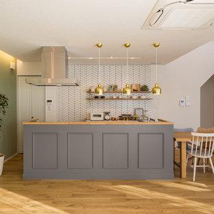 名古屋のおしゃれなキッチン (グレーのキャビネット、木材カウンター、白いキッチンパネル、無垢フローリング、茶色い床、茶色いキッチンカウンター) の写真