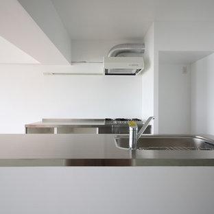 Offene, Zweizeilige Moderne Küche mit integriertem Waschbecken, flächenbündigen Schrankfronten, Edelstahlfronten, Edelstahl-Arbeitsplatte, Vinylboden, Kücheninsel und rosa Boden in Osaka