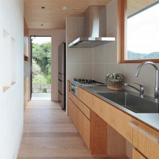 他の地域のコンテンポラリースタイルのおしゃれなI型キッチン (一体型シンク、フラットパネル扉のキャビネット、中間色木目調キャビネット、ステンレスカウンター、グレーのキッチンパネル、シルバーの調理設備、淡色無垢フローリング、アイランドなし、ベージュの床、グレーのキッチンカウンター、板張り天井) の写真