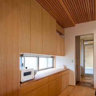 他の地域の中くらいのカントリー風おしゃれなキッチン (一体型シンク、インセット扉のキャビネット、中間色木目調キャビネット、人工大理石カウンター、白いキッチンパネル、トラバーチンのキッチンパネル、白い調理設備、無垢フローリング、ベージュの床、白いキッチンカウンター) の写真